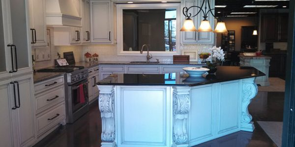 white acanthus leaf corbel on white kitchen island with black marble counter boston cabinet cures